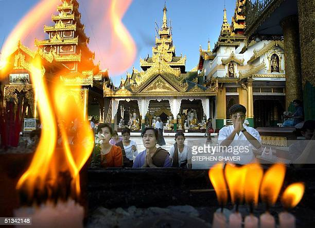 Burmese men and women kneel in front of images of Buddha as they pray and light prayer candles at the Shwedagon Paya in Yangon 04 April 2002...