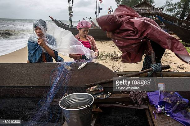 Burmese men and women remove fish from netting in high winds near the planned Dawei SEZ on August 4 2015 in Maungmagan MyanmarThe controversial...