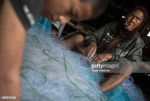 Burmese men and women remove fish from netting near the planned Dawei SEZ on August 4 2015 in Maungmagan MyanmarThe controversial multibillion dollar...