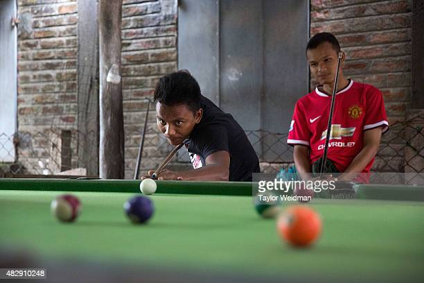 Burmese men play pool in a hall near the planned Dawei SEZ on August 4 2015 in Maungmagan MyanmarThe controversial multibillion dollar Dawei special...