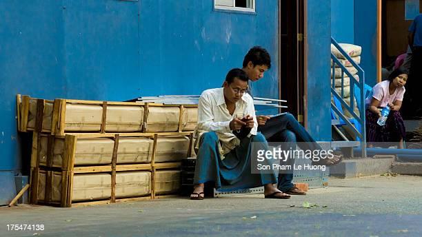 Burmese men using cell phone on the street of Yangon, Myanmar on Mar 9, 2013