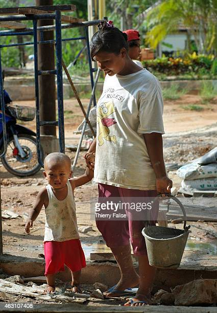Burmese migrant female in company of her child carries cement on the construction of a resort devastated by the tsunami