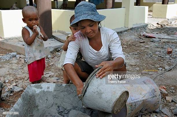 Burmese migrant female in company of her two children mixes cement on the construction of a resort devastated by the tsunami