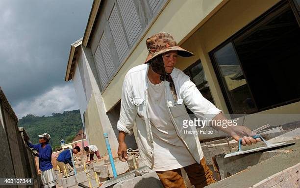 Burmese migrant female lays cement on the construction of a resort devastated by the tsunami
