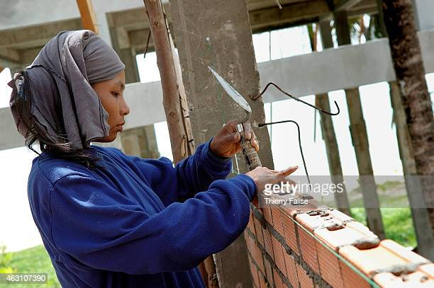 Burmese migrant female works at the construction site of a resort devastated by the tsunami on Khuk Khak beach in Bang Niang village She also has...