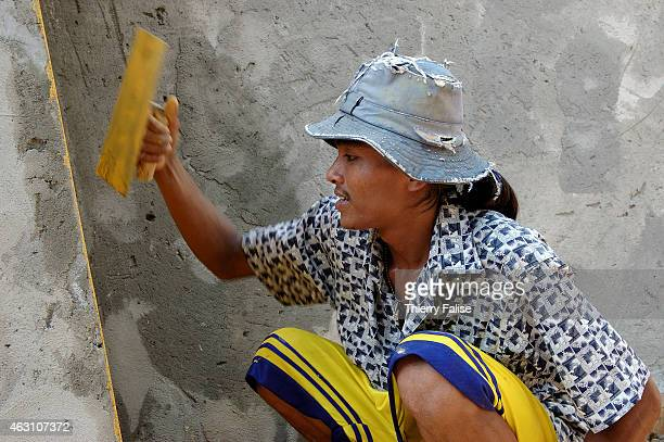 Burmese migrant paints a wall on the construction site of a resort devastated by the tsunami