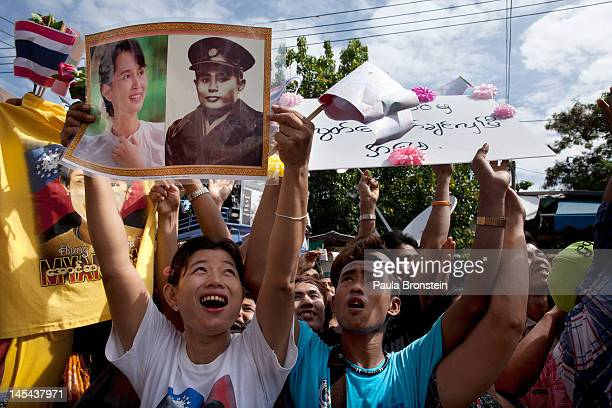 Burmese migrant workers cheer and hold aloft posters featuring Burmese prodemocracy leader Aung San Suu Kyi and her father Aung San as they wait for...