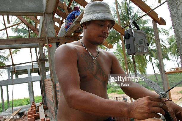 Burmese migrant works on the construction of a resort devastated by the tsunami on Khuk Khak beach in Bang Niang village While working he is...