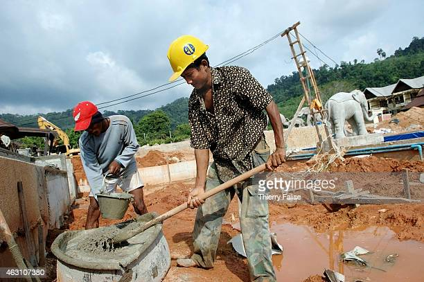 Burmese migrants mix cement on the construction of a resort devastated by the tsunami