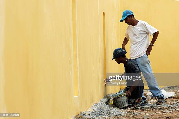 Burmese migrants paint a wall on the construction site of a resort devastated by the tsunami