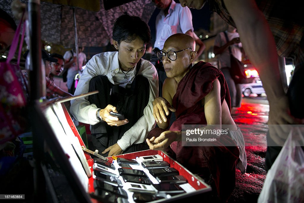 A Burmese monk shops for a used mobile phone at a street market November 30, 2012 in Yangon, Myanmar. Business is booming in this newly opened Southeast Asian country. Import restrictions have been eased resulting in many new cars seen on the streets.