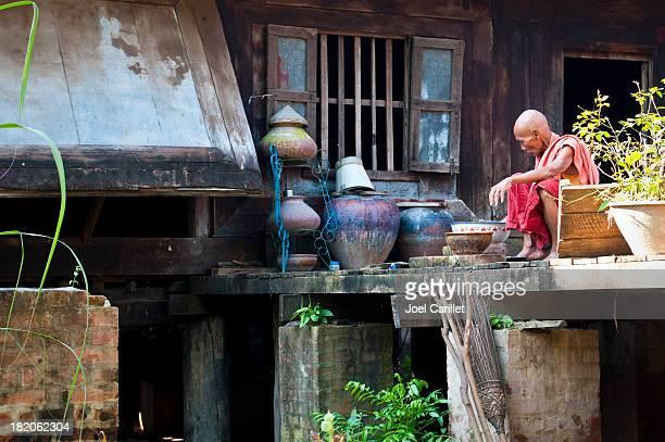 Burmese monk washing dishes at monastery in Mandalay, Burma