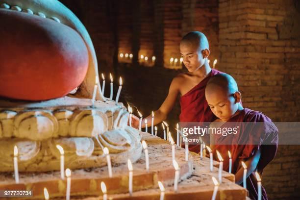 Burmese Novice Monks Lighting Candles in Temple Myanmar