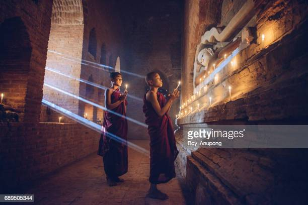 burmese novice praying for the lord buddha statue in ancient temple in bagan plain, myanmar. - myanmar culture stock pictures, royalty-free photos & images