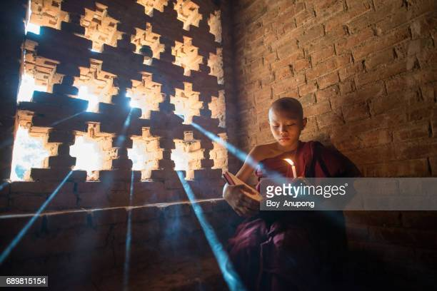 Burmese novice reading the Buddhist book inside ancient temple in Bagan plain, Myanmar.