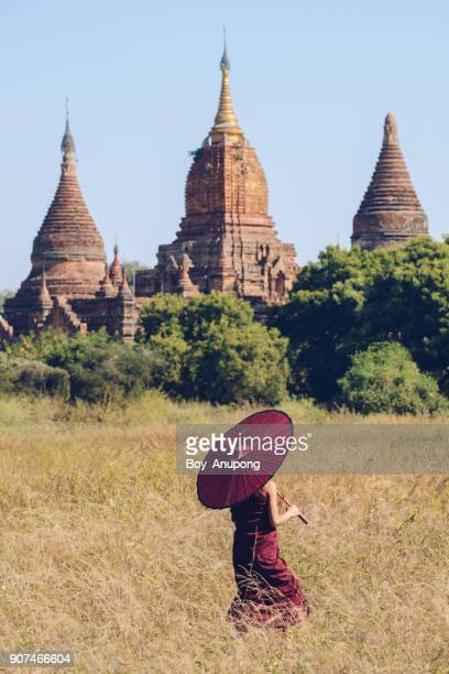 burmese novice walking past the ancient pagoda in bagan, myanmar. - バガン ストックフォトと画像