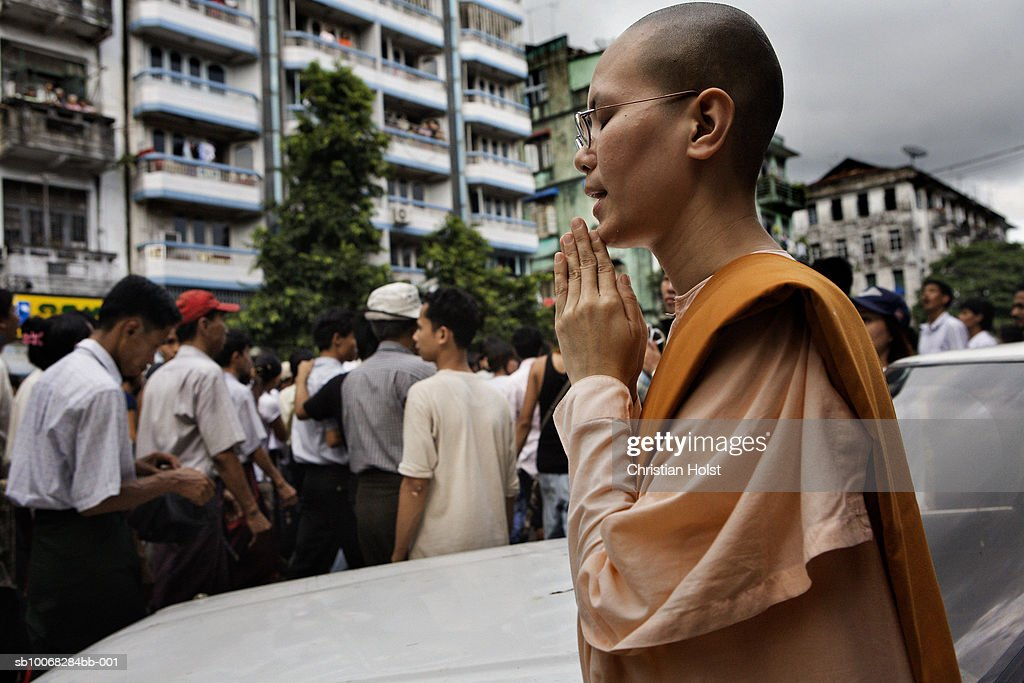 A Burmese nun prays as she watches the protesters march on Anawrahta Road near Sule Pagoda on September 26, 2007 in downtown Yangon, Myanmar. There was a standoff after heavily armed military soldiers, blockading the road, fired warning shots as the group neared the Pagoda, so the group stopped at the intersection to chant and pray over an hour until continuing the march elsewhere. People fled to flats and shops when warning shots were fired. Allegedly one person was killed and five injured at the beginning of today's march at nearby Shwedagon Pagoda. Mass protests began after the military government implemented dramatic price hikes in fuel prices on August 15th causing public bus fares to double and widespread economic hardship. The monks became involved when the leadership of initial protest marches were supressed. Uniformed security personnel were positioned throughout the former capital, patrolling watching crowds, telling them to not get involved lest action be taken against them. Military trucks parked less than a kilometer from City Hall and the Sule Pagoda, the plaza between the two buildings where in 1988, the government crushed similar pro-democracy protests by killing up to 3000 pro-democracy protesters. Government opposition has been repeatedly crushed in the country and the latest demonstrations have yet again led to mass arrests of political activists opposing the regime.