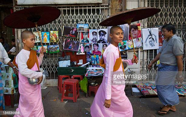 Burmese nuns walk past a street vendor's stall displaying posters of human rights activist and politician Aung San Suu Kyi and her father Aung San on...