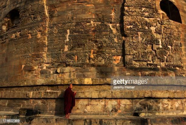 Burmese pilgrim monk makes prayer at the ornamented stupa of Sarnath