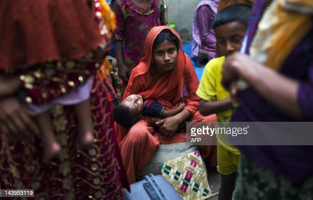 A Burmese refugee from the Rohingya community a predominantly Muslim sect in Burma holds her child as she takes refuge on a street near the United...