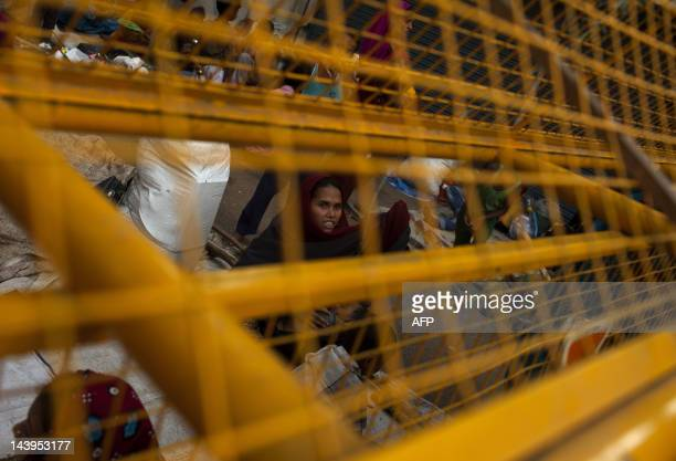 A Burmese refugee from the Rohingya community a predominantly Muslim sect in Burma sits behind a police barrier as she takes refuge on a street near...