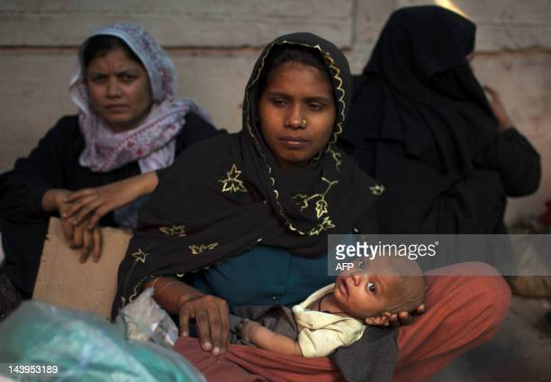 Burmese refugees from the Rohingya community a predominantly Muslim sect in Burma take refuge on a street near the United Nations High Commission for...