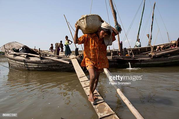Burmese Rohingya carry rocks from a boat used for a road project on May 4 2009 in Sittwe Arakan state Myanmar The Rohingya Muslim minority live in...