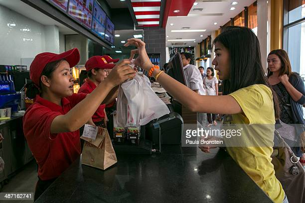 Burmese walk by the new Lotteria restaurant a large chain of fastfood restaurants April 19 2014 in Yangon Myanmar The Lotteria chain has outlets in...