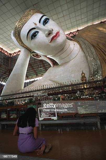 Burmese woman a meritmaker prays in front of the reclining Buddha at Chauk Htat Gyi Pagoda in Rangoon