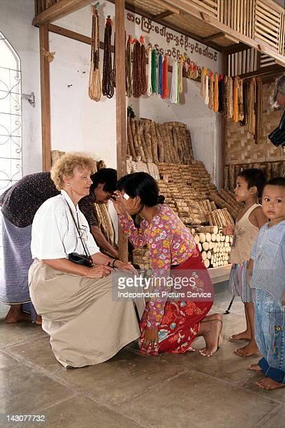 Burmese woman applying thanakha facial cream to the face of a Tourist Myanmar