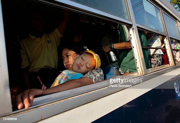 Burmese woman holds her son sleeping on a city bus March 3 2007 in Yangon Myanmar With economic sanctions crippling the Burmese economy its people...