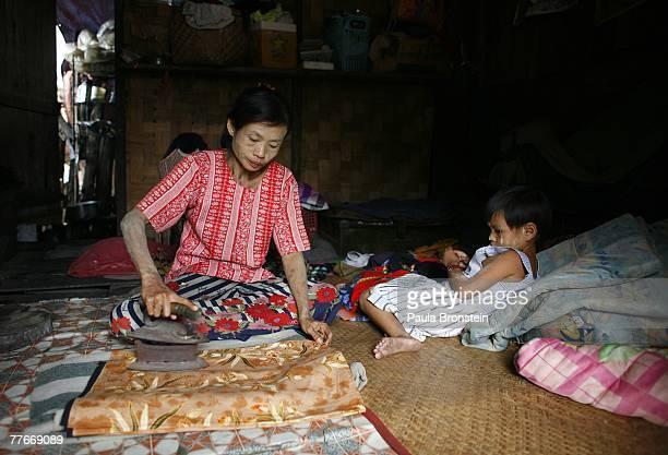 Burmese woman irons her sarong as her daughter watches inside their small shack November 3 2007 in Myawadi Myanmar Burmese cross the border into...