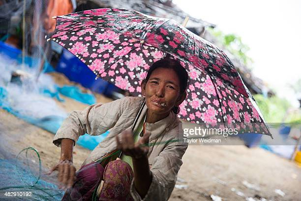 Burmese woman looks at the camera as she removes fish from netting near the planned Dawei SEZ on August 4 2015 in Maungmagan MyanmarThe controversial...