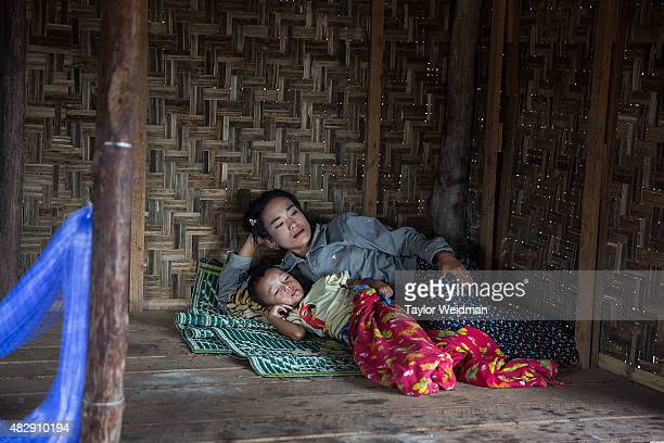 Burmese woman rests with her son in a seafood sorting area near the planned Dawei SEZ on August 4 2015 in Maungmagan MyanmarThe controversial...