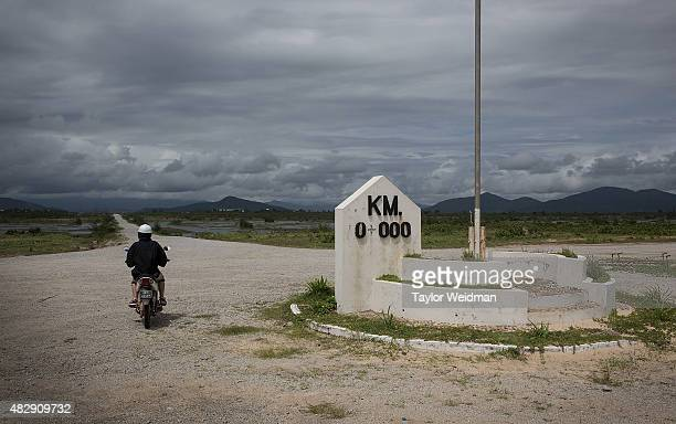Burmese woman rides her motorbike past KM 0 the beginning of the new road to the Thai border on August 3 2015 in Nabule Myanmar The controversial...