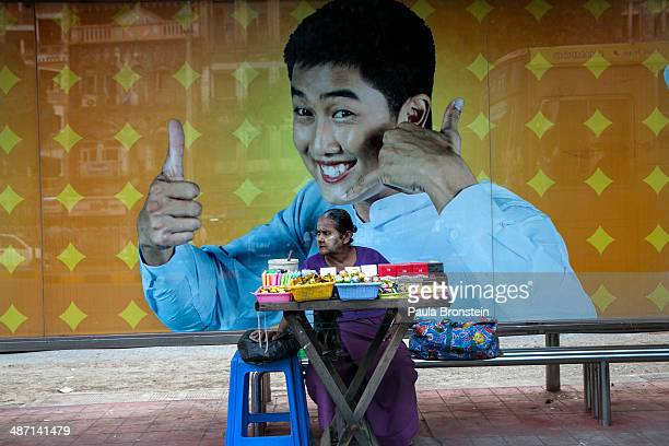 Burmese woman sells cigarettes at a bus stop against an advertisement for Qatar's Ooredoo telecom company which will begin rolling out a 3G...