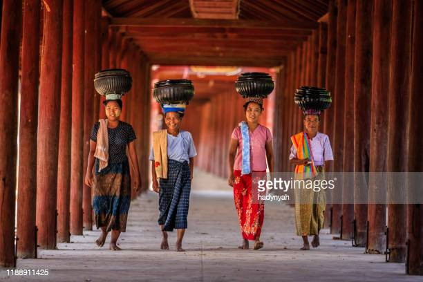 burmese women carrying bowls of rice to the monastery - myanmar stock pictures, royalty-free photos & images