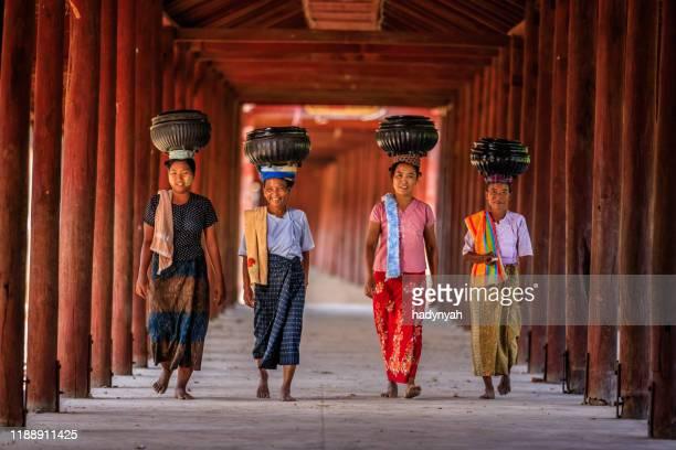 mujeres birmanas llevando cuencos de arroz al monasterio - myanmar fotografías e imágenes de stock