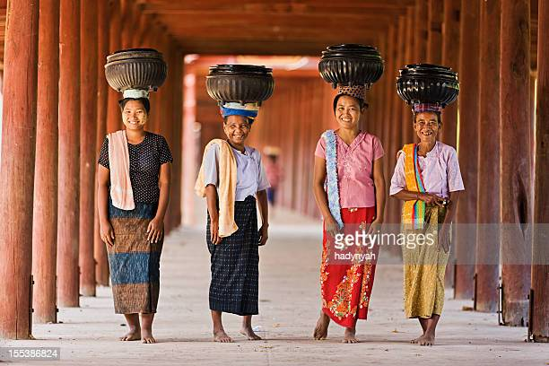 Burmese women carrying bowls of rice to the monastery