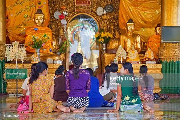 Burmese women praying barefooted in the Shwedagon Zedi Daw Pagoda at Yangon / Rangoon former capital city of Myanmar / Burma
