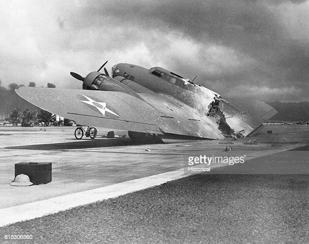 A burned B17C aircraft rests near Hangar Number Five at Hickam Field following the attack by Japanese aircraft Pearl Harbor Hawaii December 7 1941