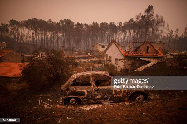 A burned car stand next to burned houses after a wildfire took dozens of lives on June 18 2017 near Castanheira de Pera in Leiria district Portugal...
