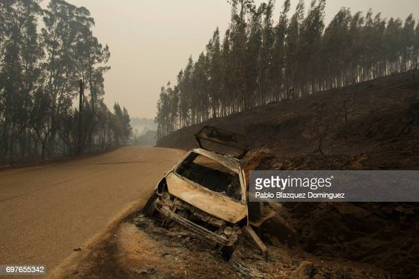 A burned car stands on the side of the road after a wildfire took dozens of lives on June 19 2017 near Castanheira de Pera in Leiria district...