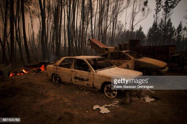 Burned cars stand next to a forest after a wildfire took dozens of lives on June 18 2017 near Castanheira de Pera in Leiria district Portugal On...