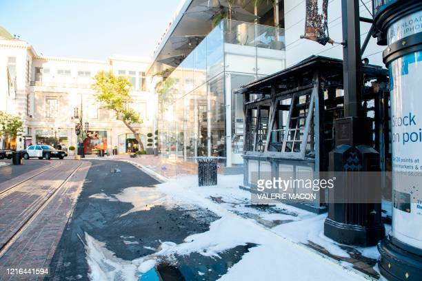 Burned down kiosk is seen at the Grove shopping center in the Fairfax District of Los Angeles on May 30, 2020 following a protest against the death...