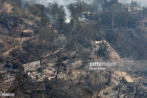 Burned homes smolder in a charred neighborhood after the Tea Fire swept through on November 14 2008 in Montecito California More than 100 homes were...
