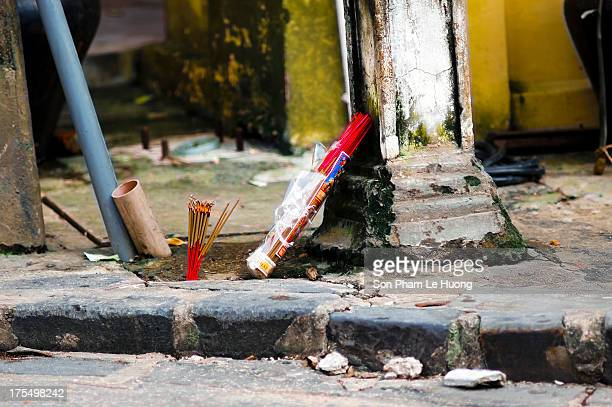 Burned incense stick on the side walk for worshiping the ghost in Hoi An, Vietnam on Nov 10, 2011