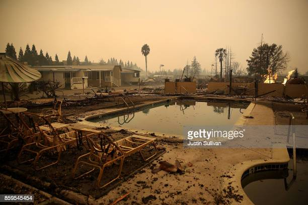Burned lawn chairs sit next to the swimming pool at the Journey's End Mobile Home Park on October 9 2017 in Santa Rosa California Ten people have...