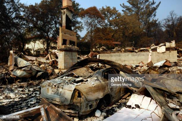 Burned out car lies in the ruins of a fire ravaged home in Napa on October 13, 2017. The home was destroyed by the Atlas fire.