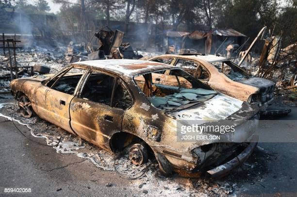 A burned out car rests on the driveway of a smoldering home in the Napa wine region in California on October 9 as multiple winddriven fires continue...
